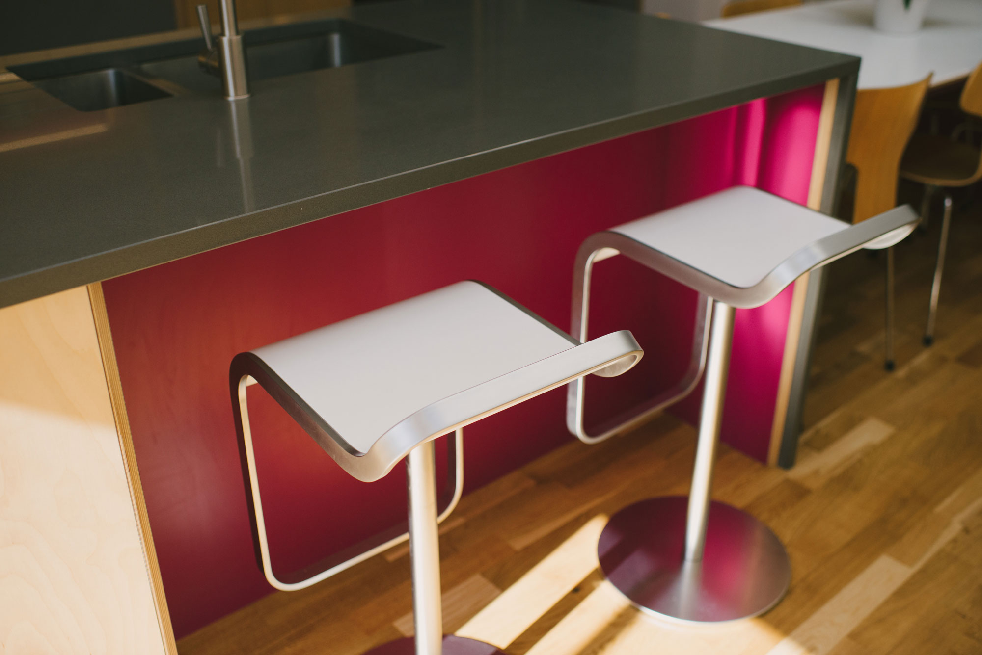 Breakfast bar stools at pink and grey plywood kitchen island unit