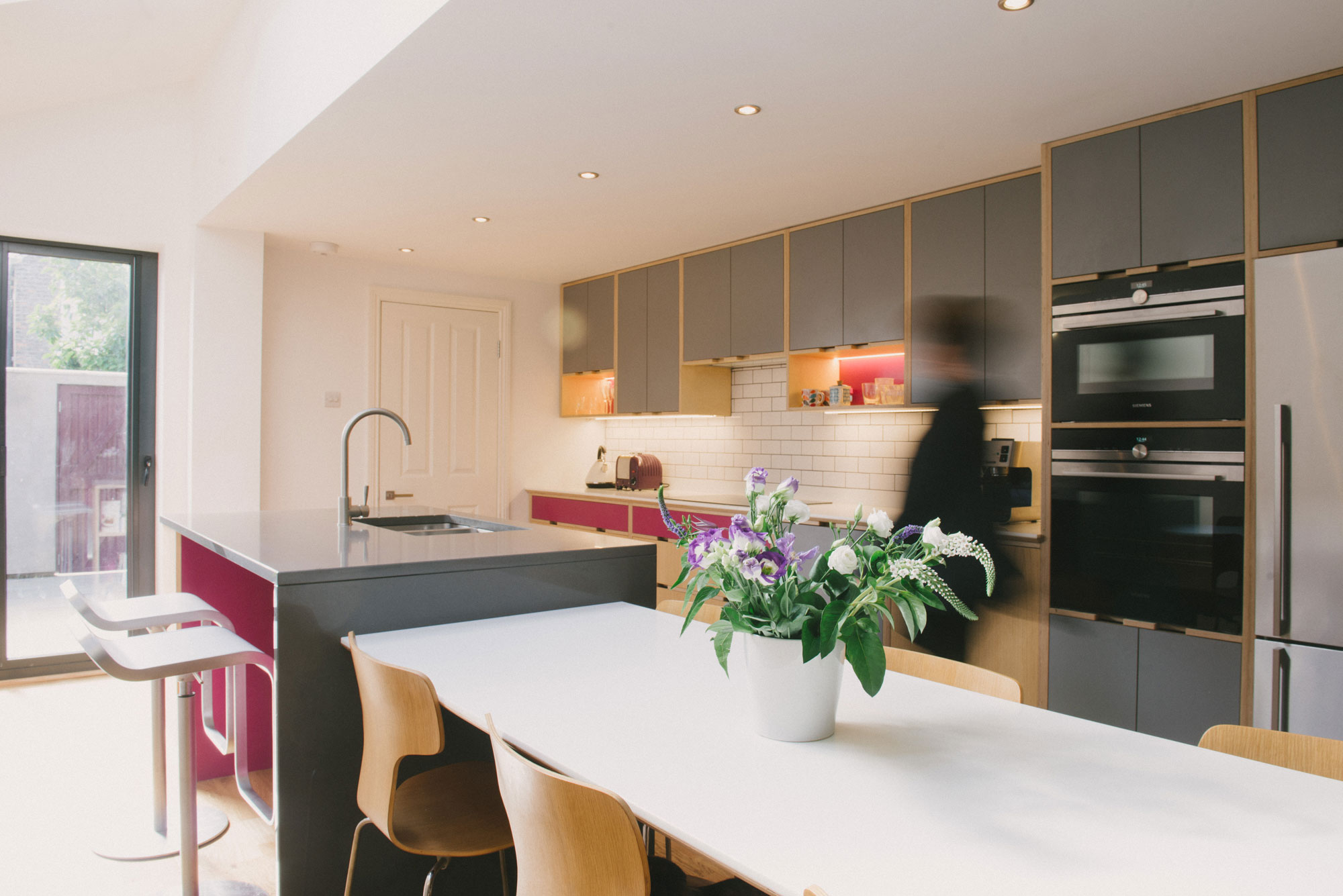 Client walks through their pink and grey plywood kitchen