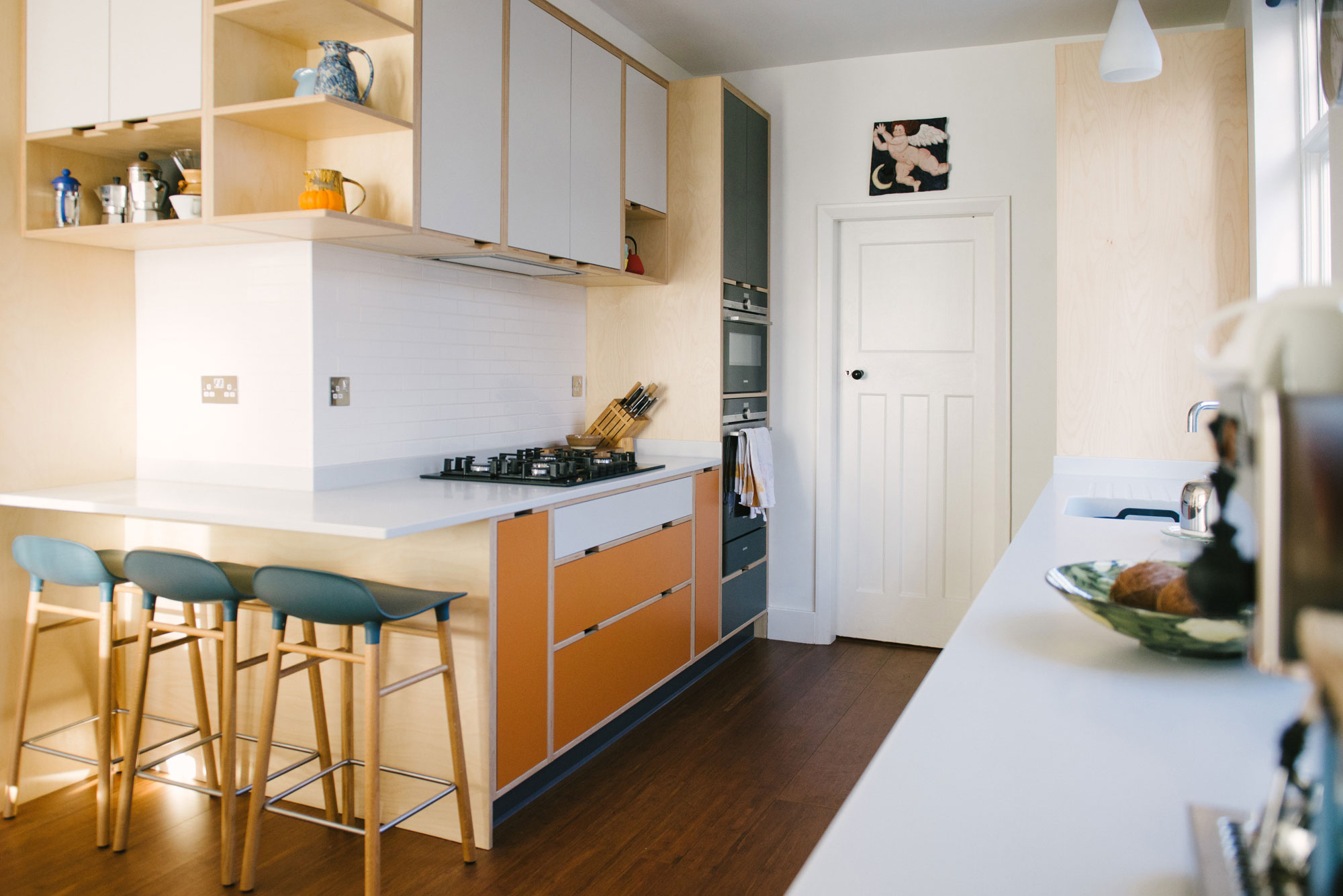 Cooking Area of Orange and White Laminated Plywood Kitchen