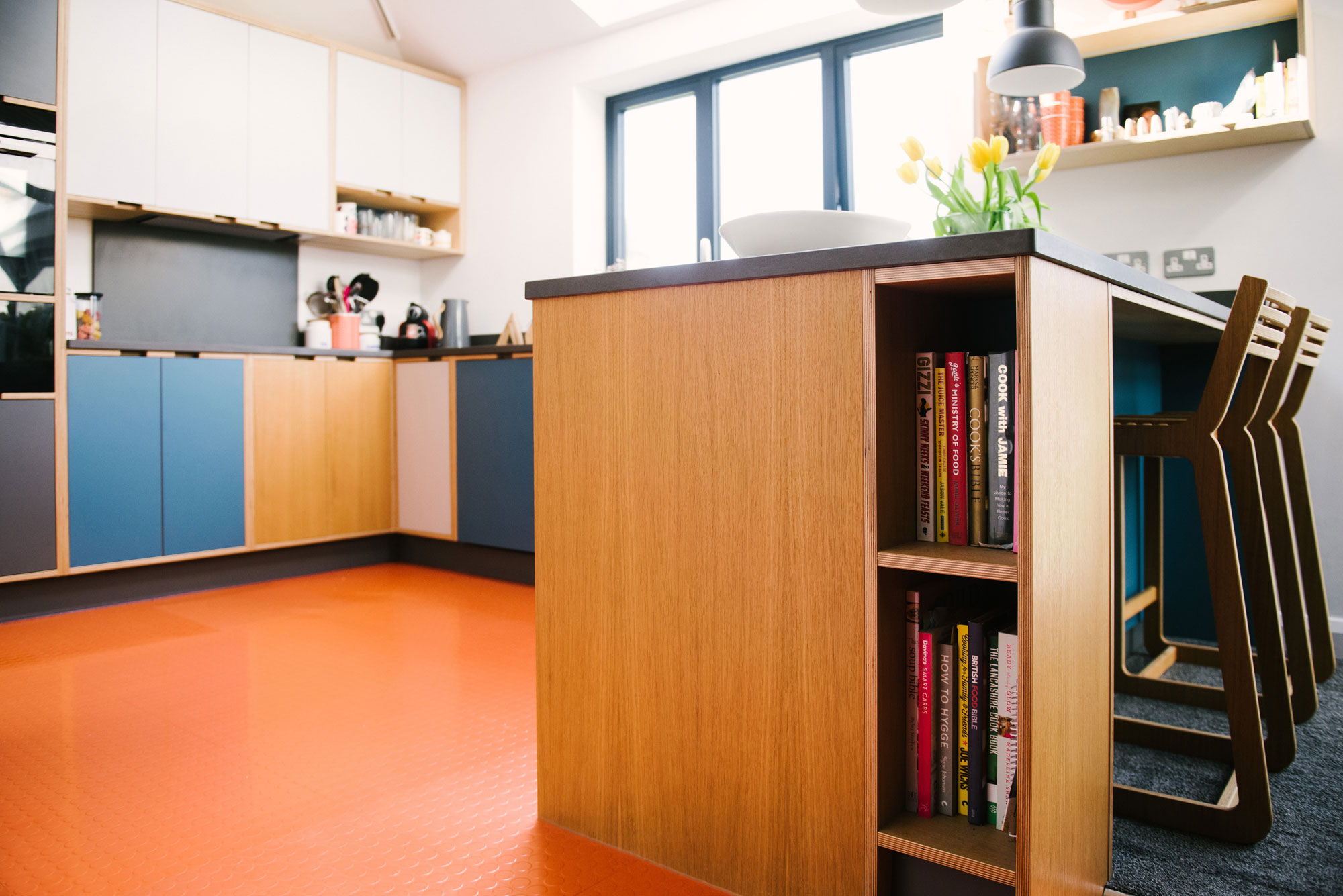 Bookcase in Island of Plywood Kitchen With Orange Floor
