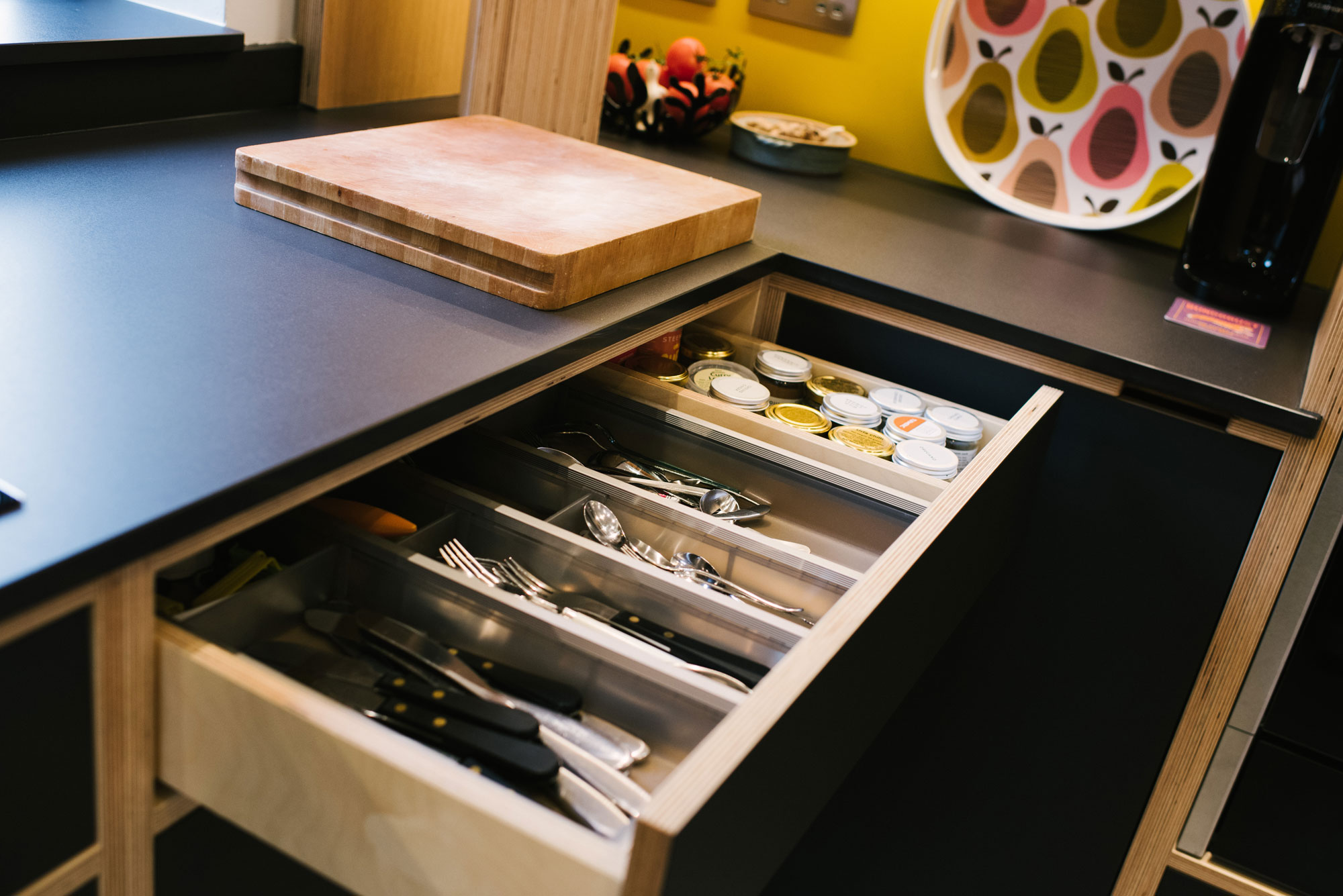 Cutlery Drawer of Black Plywood Kitchen with Yellow Splashback