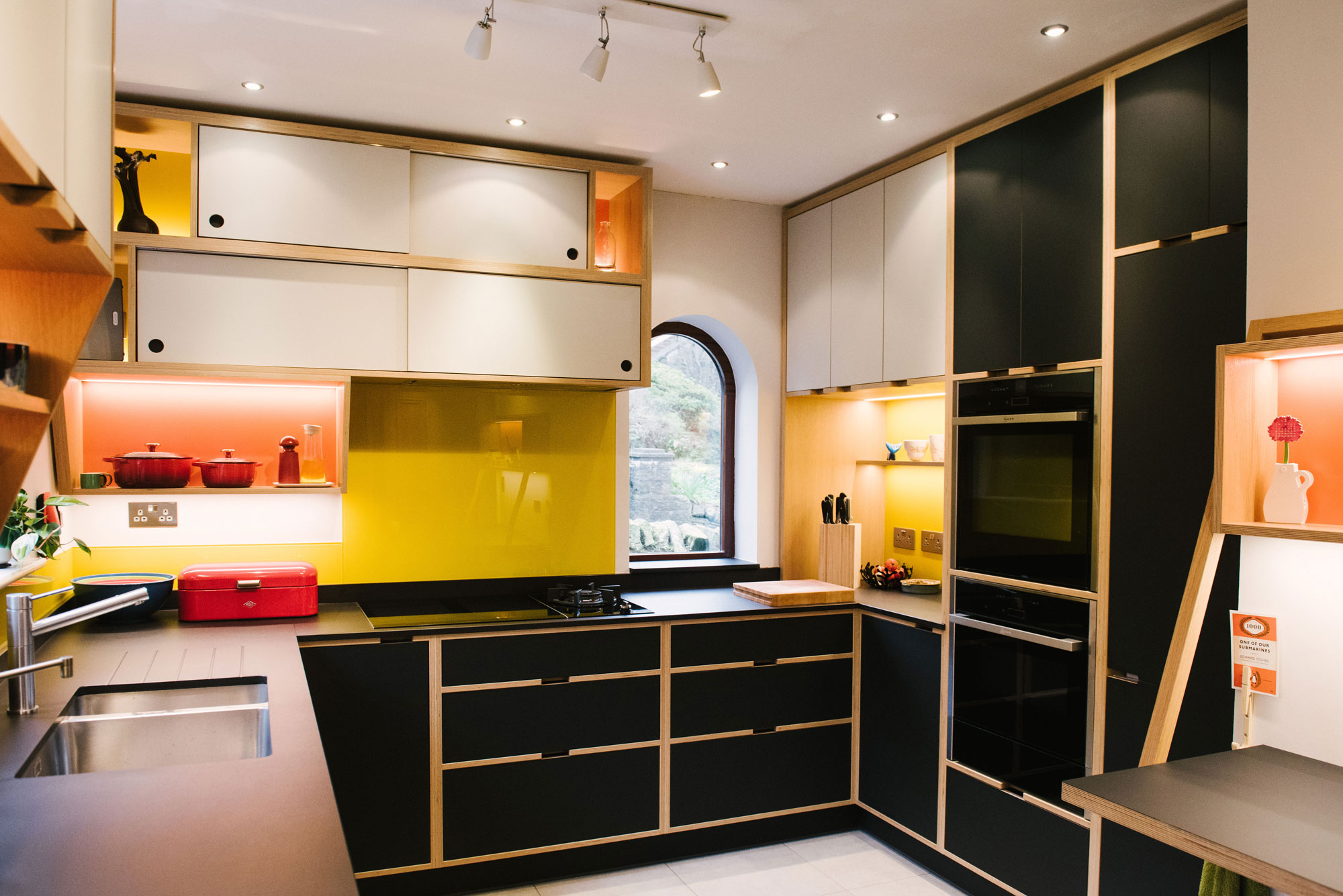Cooking Area of Black Plywood Kitchen with Yellow Splashback
