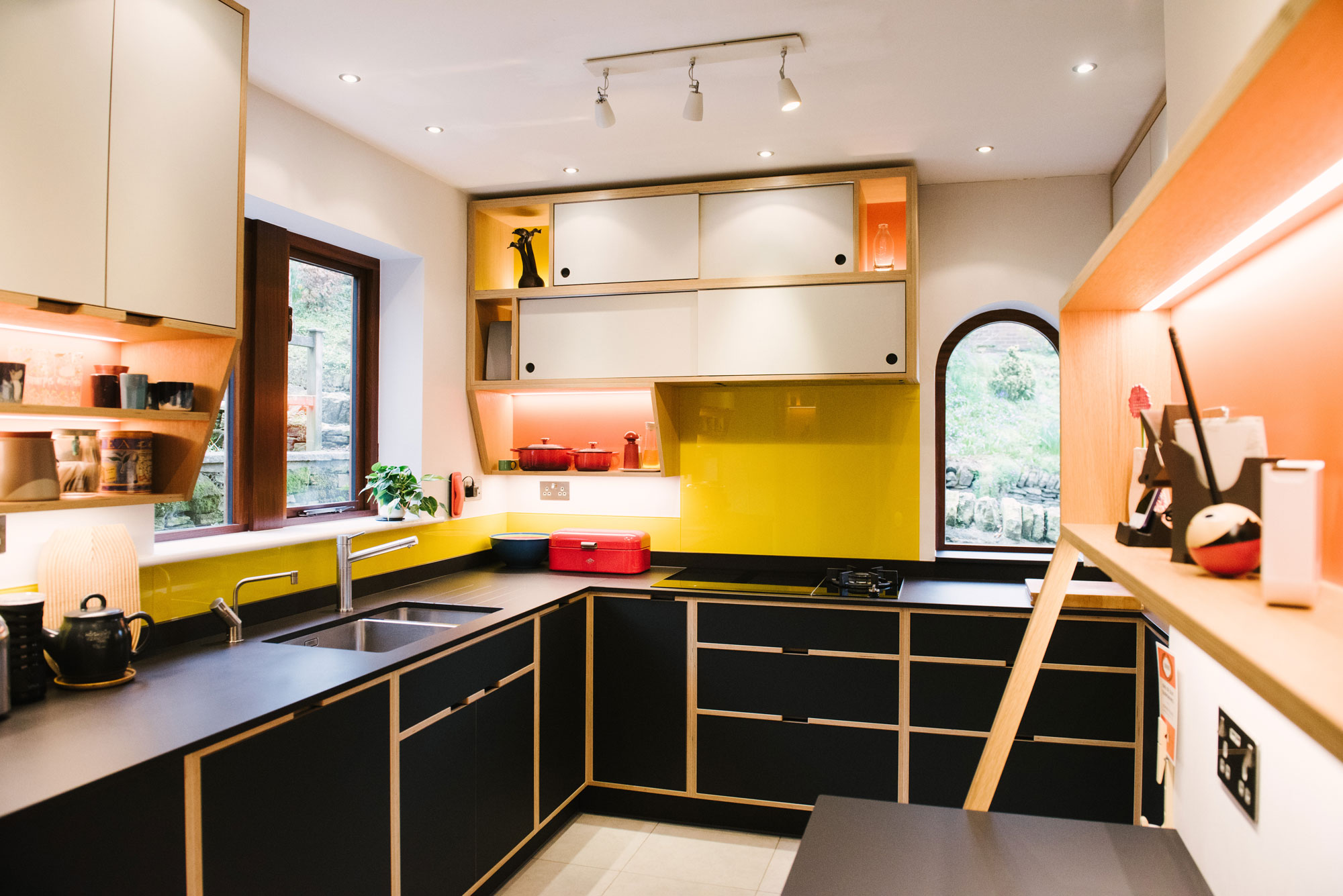Sink Area of Black Plywood Kitchen with Yellow Splashback