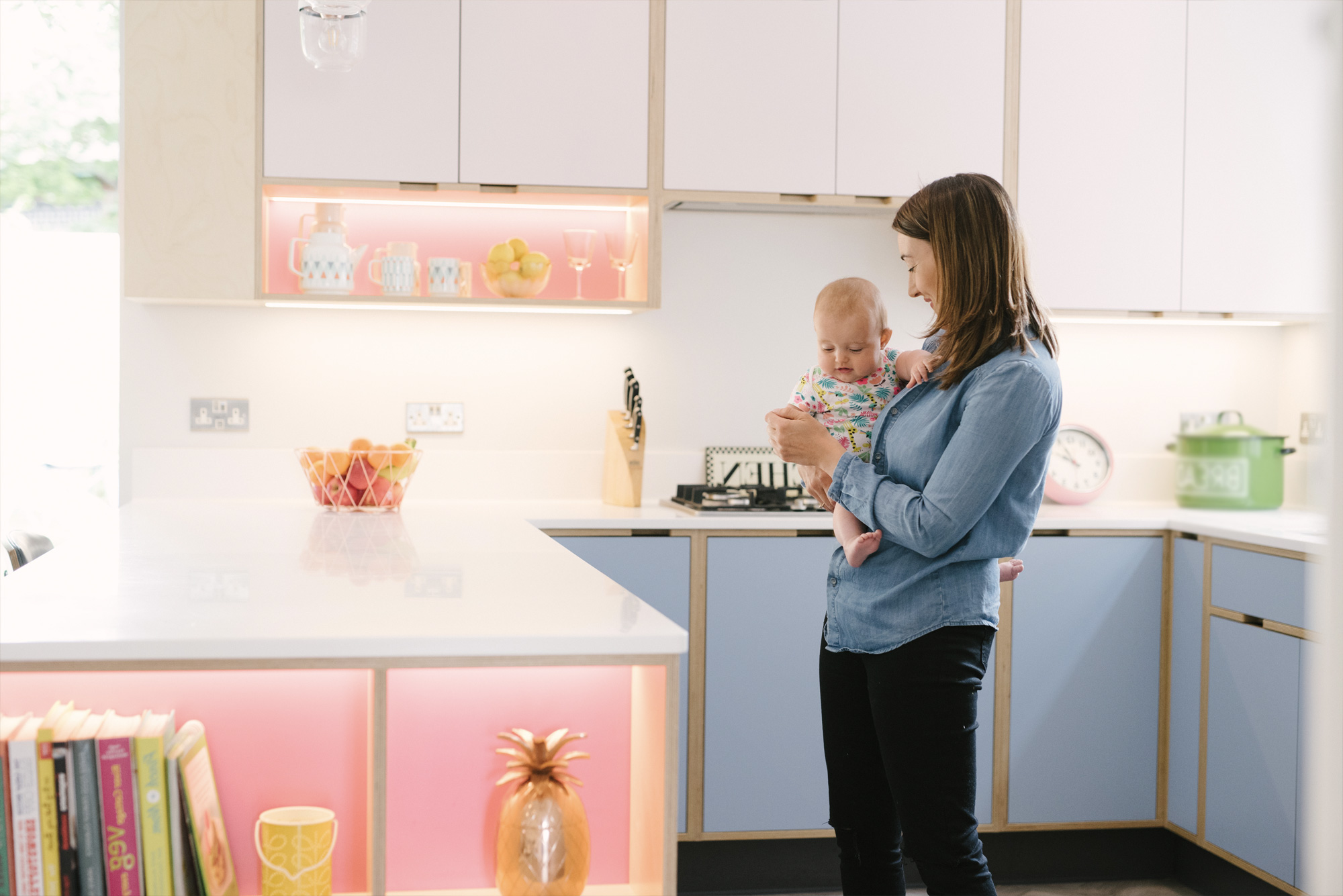 Mother and child in pink and blue plywood kitchen