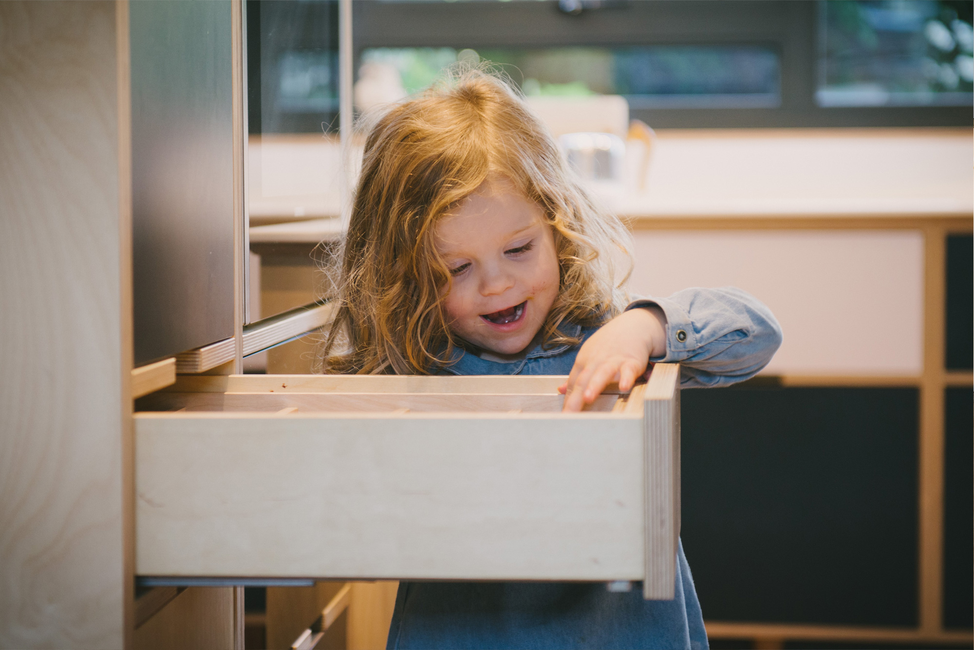 Little girl looks into plywood drawer